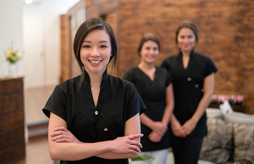 Portrait of Asian woman working at spa with a group of women in background