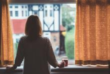 Woman with her back to the camera looking out the window with a cup of tea