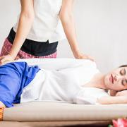 A woman lying on her side receiving massage from a female practitioner