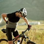 Mature man on mountain bike rubbing a sore lower back.
